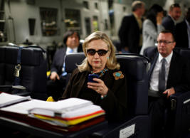 In this Oct. 18, 2011, file photo, then-Secretary of State Hillary Rodham Clinton checks her Blackberry from a desk inside a C-17 military plane upon her departure from Malta, in the Mediterranean Sea, bound for Tripoli, Libya. It's a photo that became an Internet meme: Hillary Rodham Clinton, wearing sunglasses, staring at her BlackBerry. It became a focal point for Republicans on the House committee investigating the deadly attacks in Benghazi, Libya.