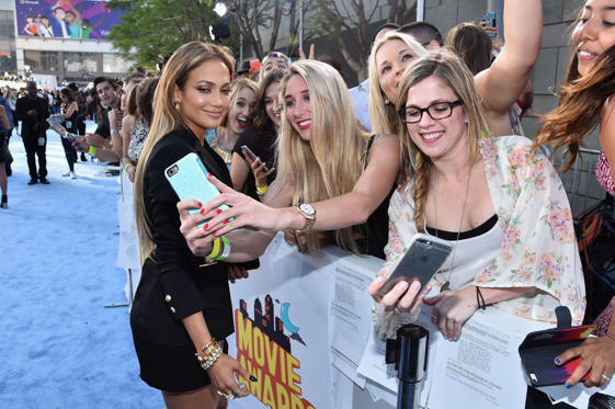 LOS ANGELES, CA - APRIL 12: Actress/singer Jennifer Lopez (L) poses with fans for a selfie photo at The 2015 MTV Movie Awards at Nokia Theatre L.A. Live on April 12, 2015 in Los Angeles, California.