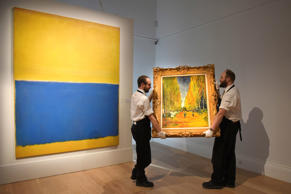 Gallery technicians carry Vincent Van Gogh's 'L'Allee des Alyscamps', painted in 1888, past Mark Rothko's 'Untitled (Yellow and Blue), 1954, as the works go on show for the exhibition between April 10 -14th at Sotheby's on April 10, 2015 in London, England. Two masterpieces of Modern art come together for the first time at Sotheby's in London; Vincent Van Gogh's L'Allee des Alyscamps and Mark Rothko's Untitled (Yellow and Blue).  With a combined estimate of 100m USD, the paintings will lead Sotheby's 500m USD flagship New York sales of Impressionist, Modern & Contemporary art in May.