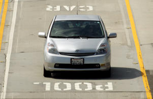 File: In a June 28, 2011 photo, a Toyota Prius hybrid auto bearing a California DMV decal on its left front bumper are seen in carpool lanes on Interstate 405 in Los Angeles.
