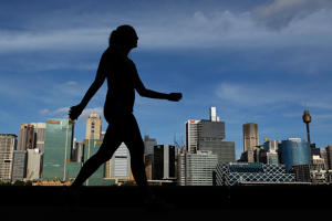 File: A woman is silhouetted as she walks past a view of the central business district in Sydney, Australia, on Tuesday, Oct. 23, 2012