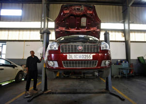 File: A man stands next to a Fiat car under repair at a workshop in Noida, on the outskirts of New Delhi April 3, 2013.
