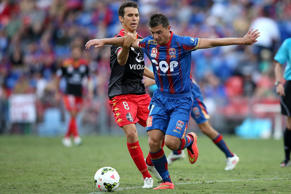 Enver Alivodic of the Jets contests the ball against Marcelo Carrusca of Adelaide United.