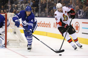 Toronto Maple Leafs defenseman Eric Brewer (2) plays the puck as Ottawa Senators right wing Bobby Ryan (6) chases him at Air Canada Centre. The Maple Leafs beat the Senators 4-3 in overtime.