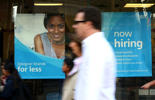 Pedestrians walk by a now hiring sign that is posted in the window of a Ross Dress for Less store on June 6, 2014 in San Francisco, California.  Justin Sullivan/Getty Images