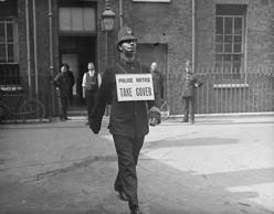 14th July 1917: A policeman walking along during an air raid with a sign round his neck saying, 'Take Cover'.