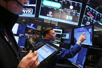 Traders work on the floor of the New York Stock Exchange (NYSE)  in New York City. Stocks were up slightly in morning trading following a steep decline yesterday partly on fears of a continued fall in global oil prices.