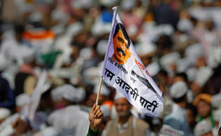 A supporter of Aam Aadmi Party waves a flag with a portrait of party leader Arvind Kejriwal during the oath-taking ceremony of Kejriwal as chief minister of Delhi in New Delhi.