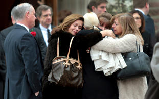 Family members of Missouri State Auditor Tom Schweich embrace outside The Church of St. Michael and St. George in Clayton, Mo., after his funeral on March 3.