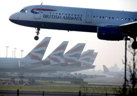 A British Airways aircraft lands at London Heathrow airport against a backdrop of British Airways branded tail fins on aircraft near terminal 5 in London.