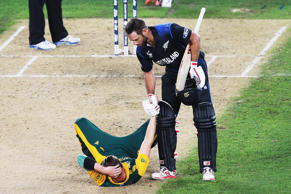 Grant Elliott of New Zealand helps Dale Steyn of South Africa up after winning the 2015 Cricket World Cup Semi Final match between New Zealand and South Africa at Eden Park.