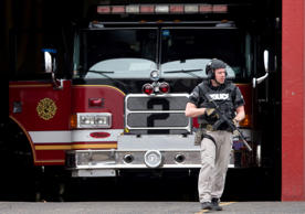 An officer walks out of the LaMott Fire Company after police escorted a man away, Tuesday, March 31, 2015, in Elkins Park, Pa. Authorities say a former volunteer firefighter held four firefighters hostage at the Philadelphia-area firehouse before surrendering to police. No injuries were reported. Matt Rourke/AP