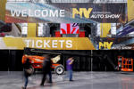 People walk by the ticketing entrance for the New York International Auto Show at the Javits Center ahead of the event in New York March 30, 2015.