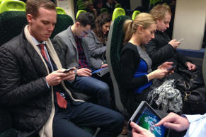 Commuters on a train to London looking at their mobile phones and iPad texting and playing games