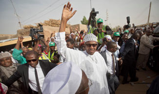 In this Saturday, March 28, 2015 file photo, opposition candidate Gen. Muhammadu Buhari waves to supporters after casting his vote in his home town of Daura, northern Nigeria.