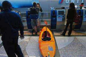 A man checks his kayak in at the Denver Airport.