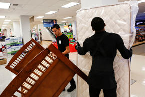 Employees prepare to load a bed a mattress set for a customer at the Sears store inside the Del Amo shopping mall in Torrance, California, U.S.