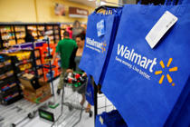 Customers push carts past reusable Walmart shopping bags during the grand opening of a Wal-Mart Stores Inc. location in the Chinatown neighborhood of Los Angeles on Sept. 19, 2013.