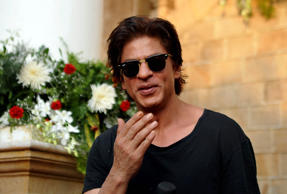 File: Indian Bollywood actor Shah Rukh Khan poses for a photograph during a photocall for his 49th birthday celebrations at his home in Mumbai on November 2, 2014.