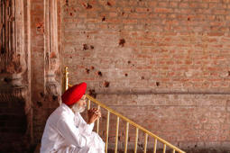 File: A Sikh man sits beside the wall of one of the complex of Golden Temple hit by the bullet shots during the operation Blue Star in the northern Indian city of Amritsar June 6, 2010.
