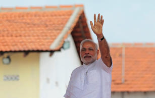 File: Indian Prime Minister Narendra Modi waves to the gathering during the handing over of homes under a housing scheme funded by the Indian government for war victims in Llavalai, northwest of Jaffna, Sri Lanka