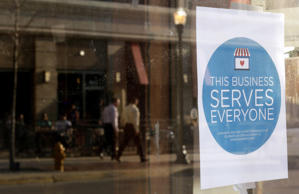 "A sign reading ""This business serves everyone"" is placed in the window of Bernadette's Barbershop in downtown Lafayette, Indiana March 31, 2015."