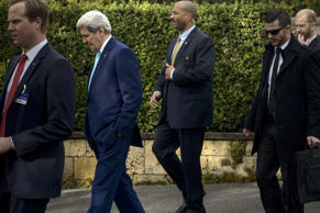 US Secretary of State John Kerry, 2nd left, is surrounded by security staff as he walks from the Olympic Museum to the Beau Rivage Palace Hotel while taking a break during an extended round of talks on Wednesday April 1, 2015, in Lausanne, Switzerland.