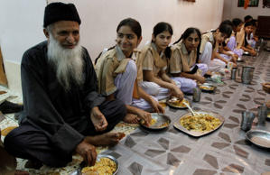 File: In this photo taken on July 24, 2010, humanitarian leader Abdul Sattar Edhi, left, has a meal with children living in one of his charity houses in Karachi, Pakistan. Edhi is a devout Muslim, but critical of Islamic clerics in general, not just extremists.