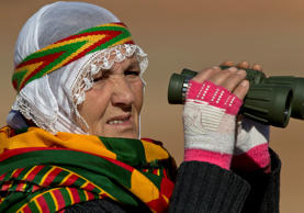 File: A woman wearing a traditional Kurdish dress watches fighting on the outskirts of Kobani, seen from the Kara Ali village on the Turkey-Syria border Tuesday, Nov. 4, 2014