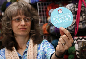"Elizabeth Ladd, owner of River Knits Fine Yarns, poses while holding up a ""This businesses serves everyone"" sticker she plans to place outside her business in downtown Lafayette, Indiana, March 31, 2015."