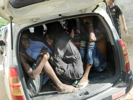Students of the Garissa University College take shelter in a vehicle after fleeing from an attack by gunmen in Garissa, Kenya, Thursday, April 2, 2015.