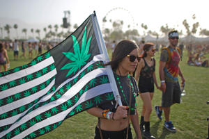 A woman carries a flag bearing marijuana symbols at the Coachella Valley Music & Arts Festival in Indio, Calif. in 2014.