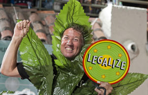 A man costumed as a marijuana leaf offers support for legalization as he rides a float during the Fantasy Fest Parade on Oct. 25, 2014, in Key West, Fla.