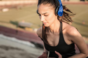 Young woman wearing headphones running.