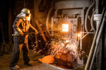 Steel worker in front of furnace in steel foundry