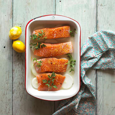 Overhead view of salmon steaks being prepared for baking with lemon and onion.