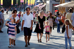 People enjoy the Summer weather walking along a busy shopping district  in Oslo,...