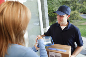 Woman receiving home delivery package from delivery service