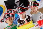 A group of boys dressed in pirate hats celebrate at a birthday party.