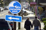 A couple walks hand in hand past one of many tsunami evacuation route signs in Cannon Beach, Ore., Friday, April 1, 2005.