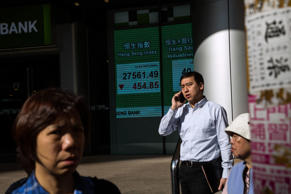 People pass by a display showing the closing figures of the Hang Seng index in H...