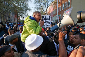 Robert Dunn is hoisted up to speak to the marchers around the Baltimore Police Department's Western District police station during a march for Freddie Gray, Wednesday, April 22, 2015, in Baltimore.
