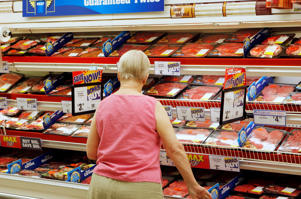 A shopper looks at the meat section in a supermarket.