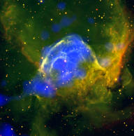 This brightly colored scene shows a giant cloud of glowing gas and dust known as NGC 2359. This is also dubbed the Thor's Helmet nebula, due to the arching arms of gas stemming from the central bulge and curving towards the top left and right of the frame, creating a shape reminiscent of the Norse god's winged helmet. The neon colours in this image are not just beautiful, they also tell us about the nebula's composition. The bright blue patches show X-ray emission, spotted by the EPIC cameras on ESA's XMM-Newton space observatory, while the pale red and green regions trace the glow from ionised hydrogen and oxygen, as seen by the Stars and Shadows Remote Observatory South at the Cerro Tololo Inter-American Observatory.  The intense X-ray emission detected by XMM-Newton is emanating from a star at the centre of the nebula. This star, a Wolf-Rayet star named HD 56925, is old, massive and pushing out incredible amounts of material at a staggering pace: the star loses a mass equivalent to that of the Sun in less than 100 000 years, in the form of a wind moving faster than 1500 km/s. The blue patches in this image highlight the nebula's hottest regions: the central bubble and a blowout to its lower left. NGC 2359's gas is thought to reach temperatures ranging from several million up to tens of millions of degrees.