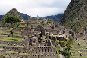 Tourists walk through ruins at the Machu Picchu site, one of the New Seven Wonders of the World, in Peru.