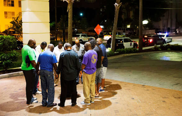 Worshippers gather to pray in a hotel parking lot across the street from the scene of a shooting Wednesday, June 17, 2015, in Charleston, S.C.