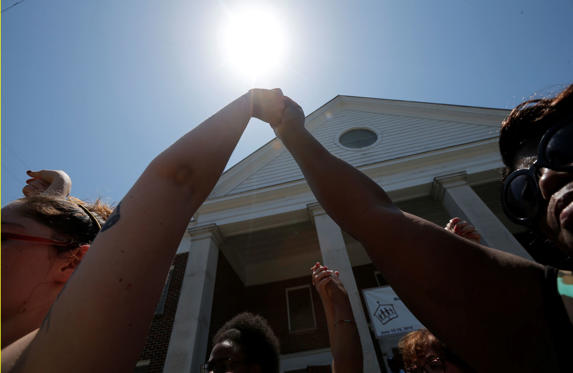 Mourners raise hands outside Morris Brown AME Church before attending a vigil the day after a mass shooting in Charleston, South Carolina June 18, 2015. A 21-year-old white gunman accused of killing nine people at a historic African-American church in Charleston, South Carolina, was arrested on Thursday, said U.S. officials, who are investigating the attack as a hate crime.    REUTERS/Brian Snyder  - RTX1H4YU