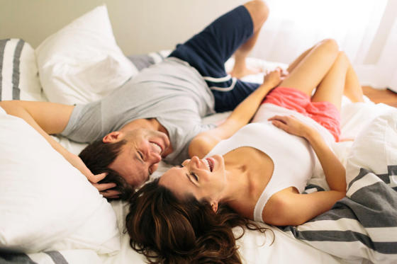Couple lays down laughing in bed