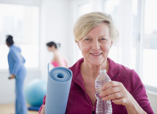 Caucasian woman with yoga mat drinking water