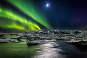 Northern lights with the moon illuminating the skies and icebergs at the Jokulsarlon Glacial lagoon, Iceland